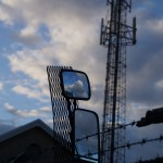 radio mast, barbed wire and rear-view mirror reflecting cloudy sky
