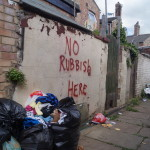 'no rubbish here' spray painted message on wall in alley between sir lewis street and cresswell street. rubbish bags in foreground