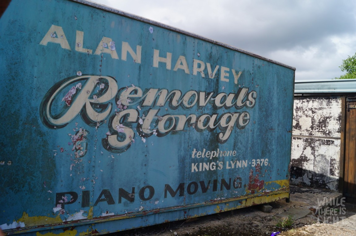 "hand painted sign on storage container. reads ""alan harvey removals & storage. piano moving"""