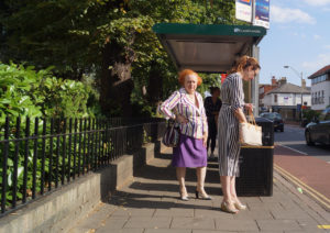 women at bus stop in cambridge