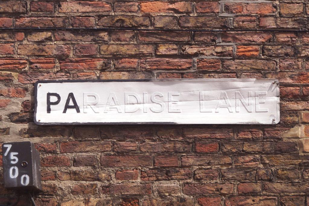 damaged paradise lane kings lynn street sign on wall