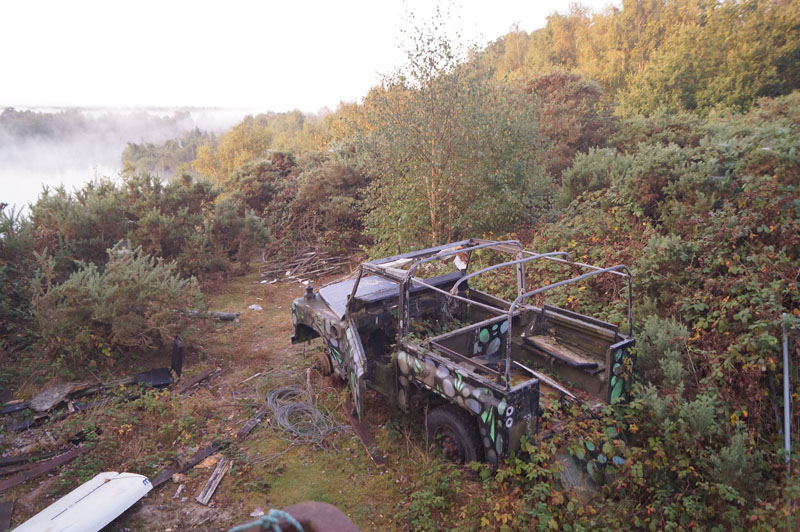 abandoned landrover amongst the bushes at leziate country park sailing club. mist is rising from the lake