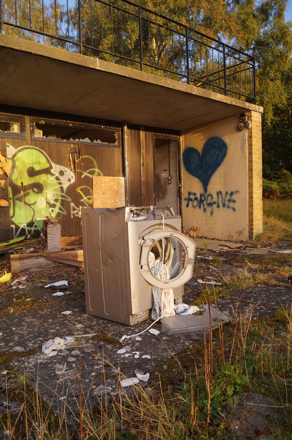 washing machine at derelict leziate sailing club with spilled load and 'forgive' graffiti