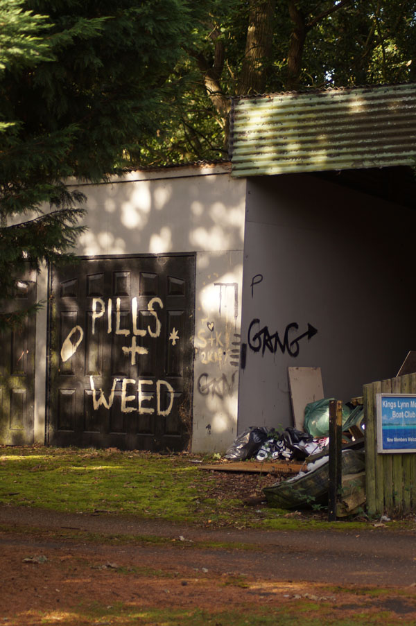 'pills + weed' graffiti on garage door at derelict leziate sailing club site